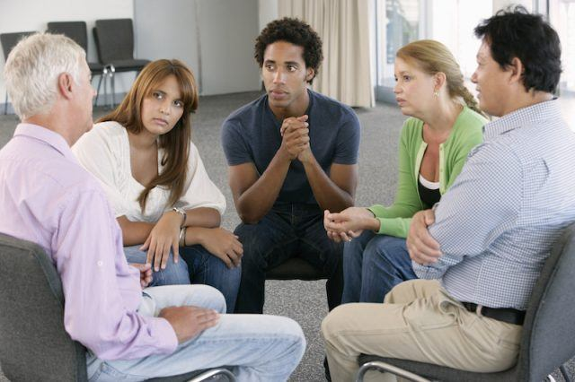 A therapy group meeting speaking with a therapist.