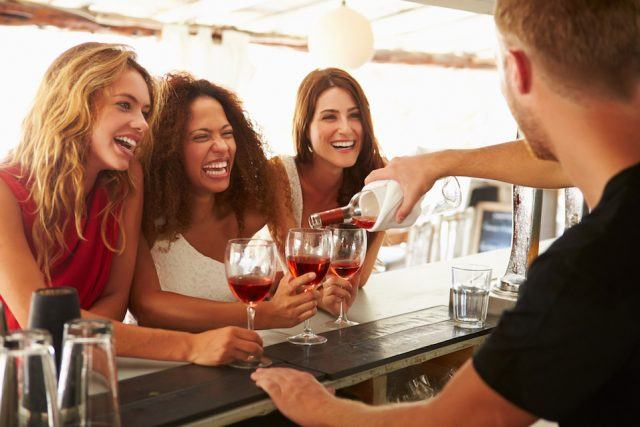 Three friends enjoying wine at an outdoor bar.