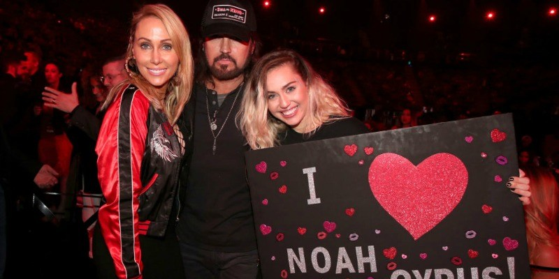 "Tish, Billy Ray, and Miley Cyrus pose together as Miley holds up a poster saying ""I heart Noah Cyrus."""