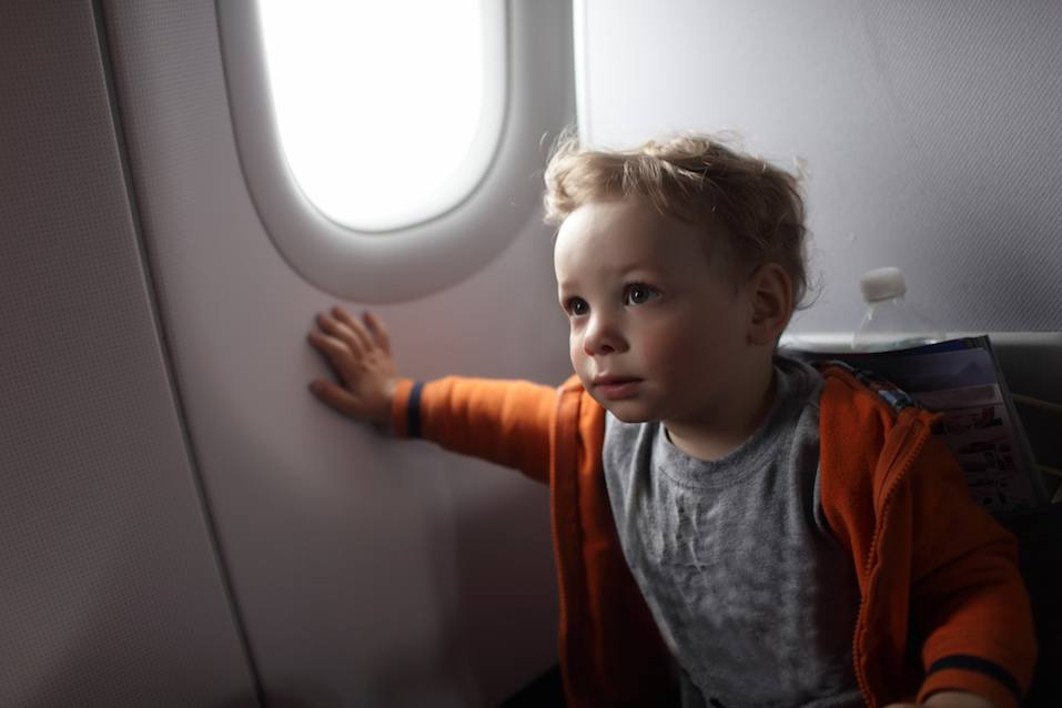 Toddler is on the flight at an airplane