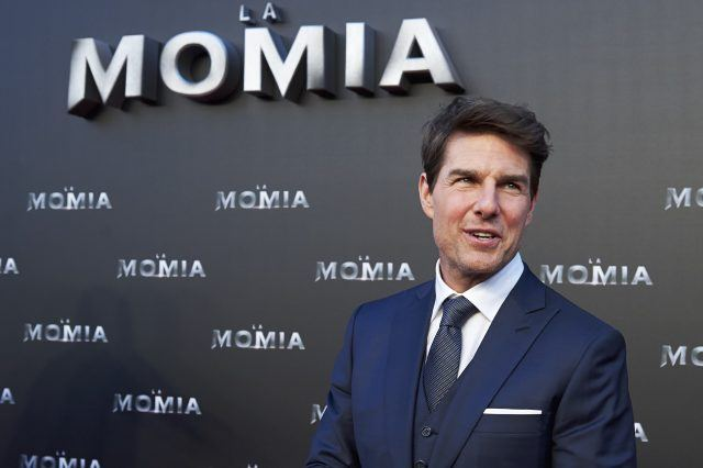 Tom Cruise smiles and looks to the side while posing for photos at a movie premiere.
