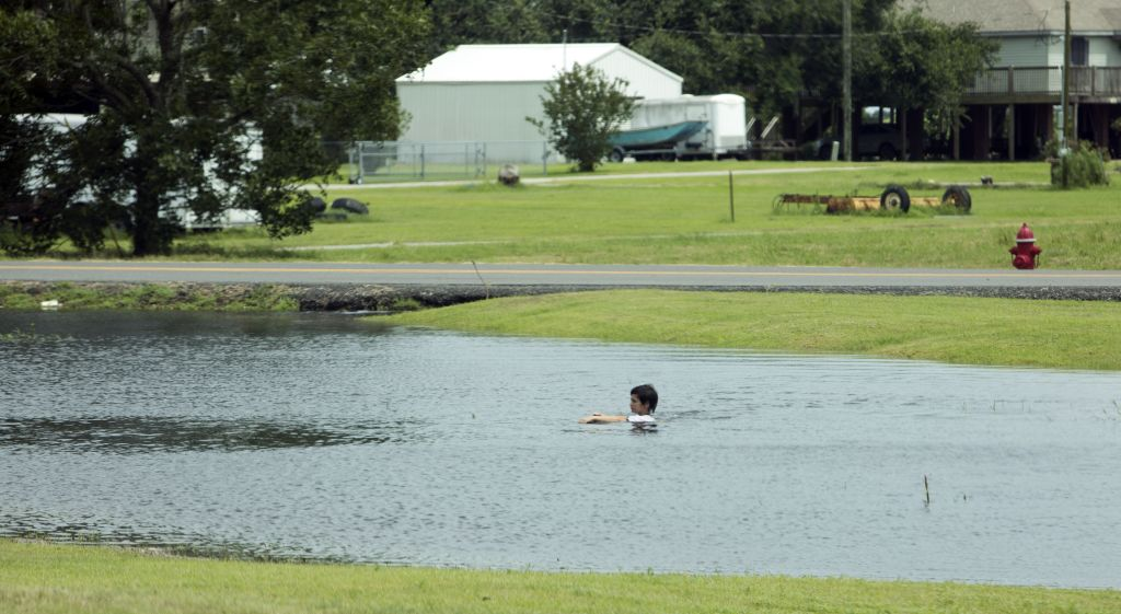 Boy swims in pond formed by storm