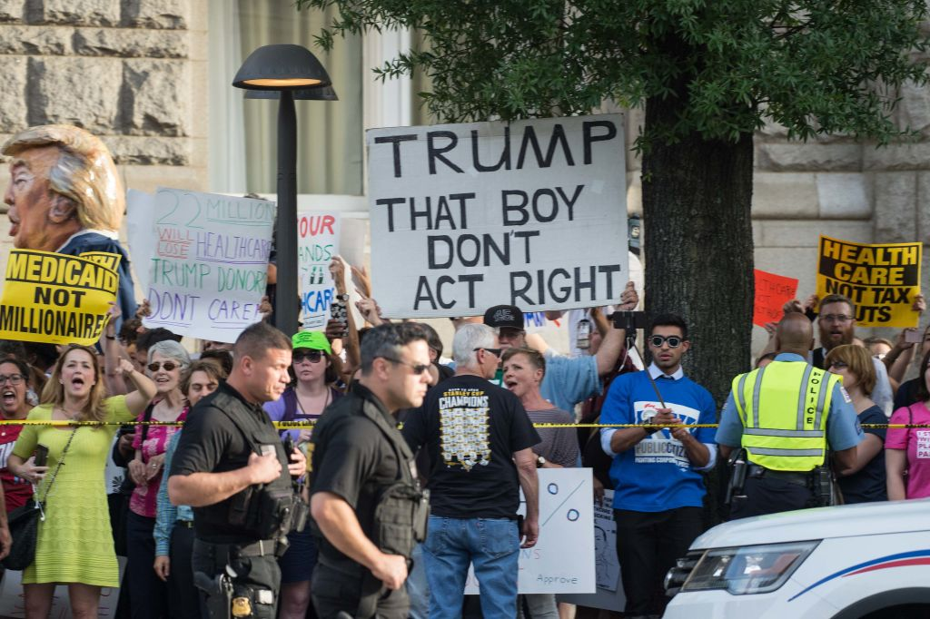 protesters hold up signs against donald trump