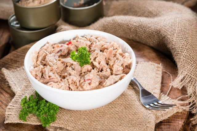 A white bowl full of tuna on a table with a fork.