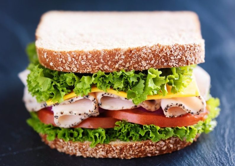 a sandwich made with deli meat, cheese, and veggies