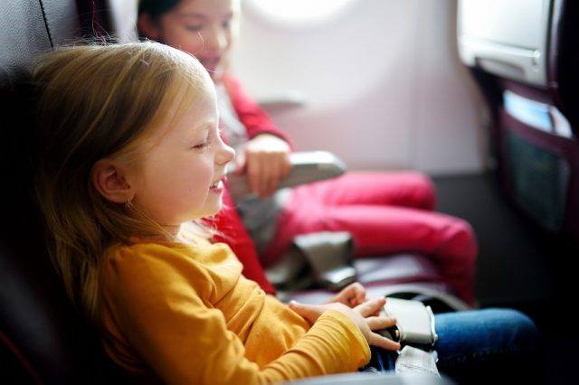 Little girls traveling by an airplane.