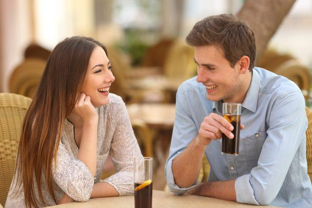 Happy couple or friends talking in a restaurant and looking each other