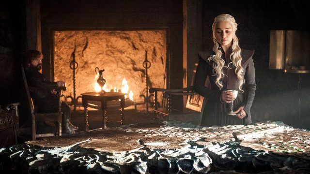 Daenerys stands in front of a fireplace and holds a cup