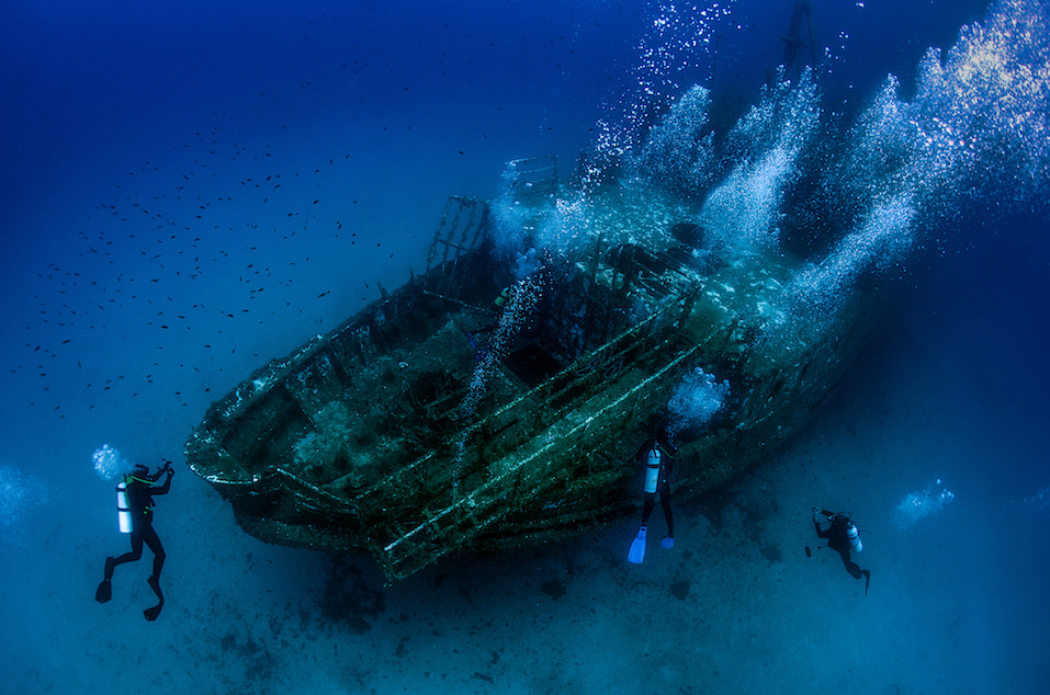 Underwater wreck with divers exploring