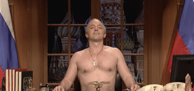 SNL's portrayer of Vladimir Putin sits shirtless in front of a desk.