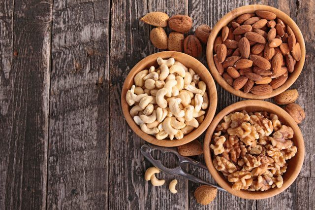 Walnuts, cashews and almonds in three bowls.