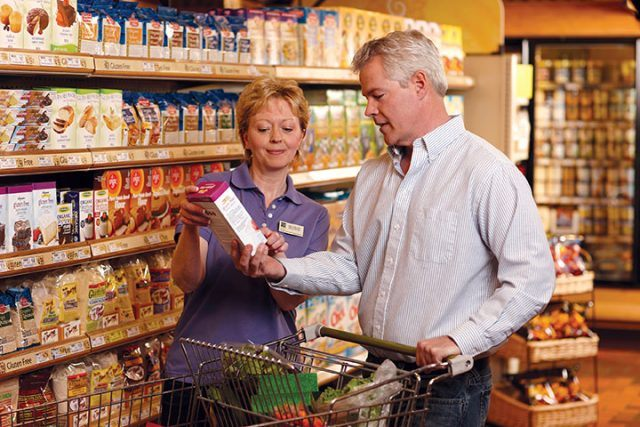 Wegmans employee assists a man in the natural section of the store