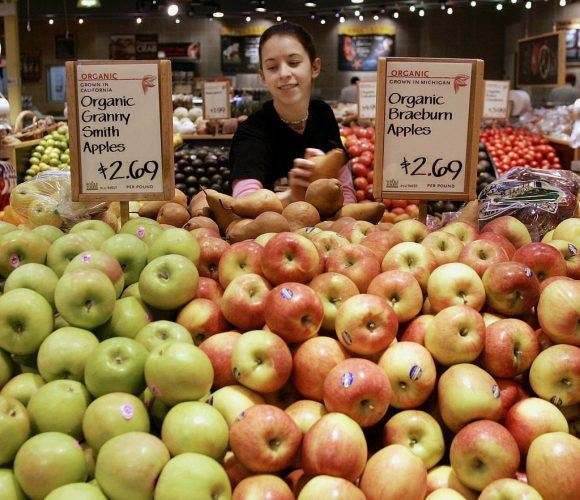 A woman picks out fruit at a supermarket.