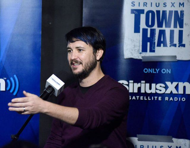 Wil Wheaton speaks into a microphone while answering questions from the press at an event in LA.