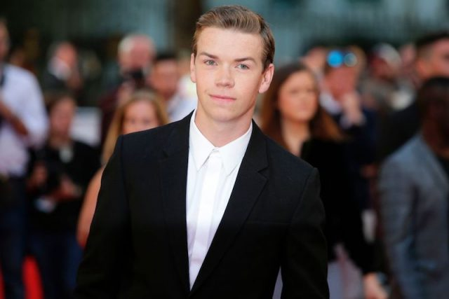 Will Poulter stands in a suit at a movie premiere.