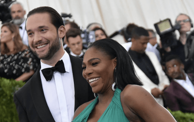 Serena Williams and Alexis Ohanian smiling on a red carpet.