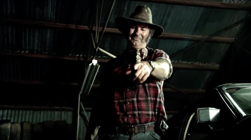 John Jarratt as Mick Taylor holding a bloody knife in Wolf Creek