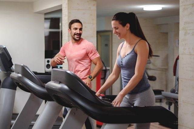 A man and woman talk while using treadmill machines.