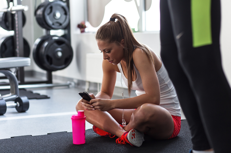 Woman sitting at the gym on her phone