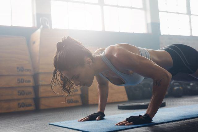 A woman in a gym getting into a push up position.