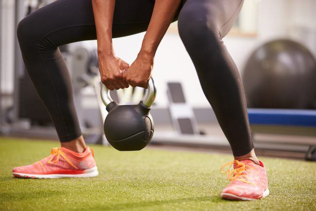 Woman exercising with a kettlebell weight
