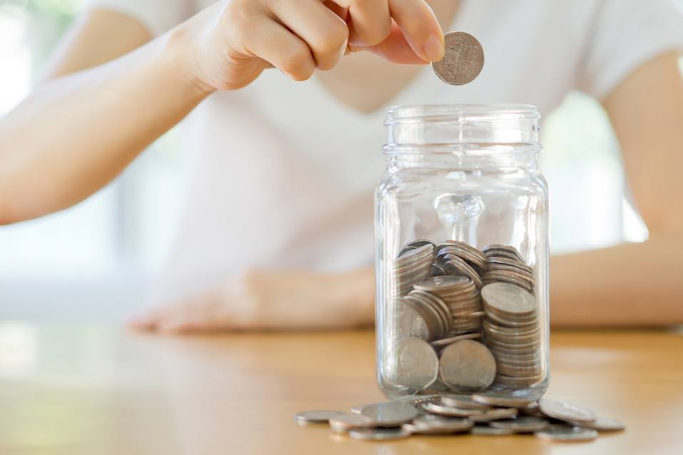Woman hands with coins in glass jar,