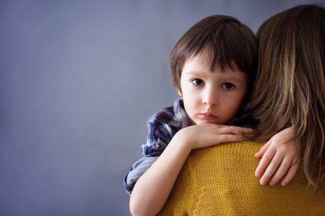 A sad child clings to his mother.