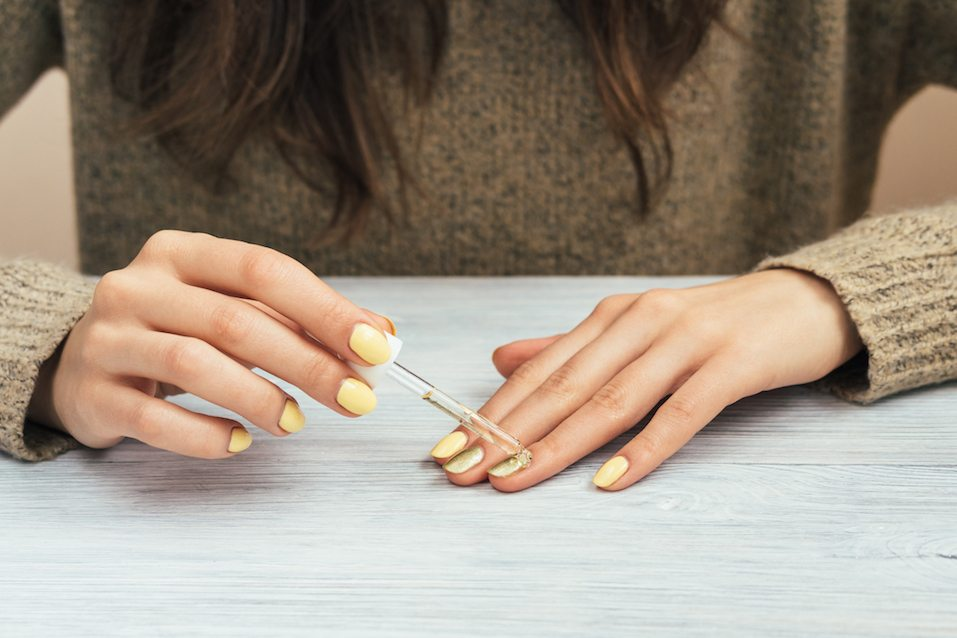 Woman in a brown sweater with yellow manicure applying cosmetic