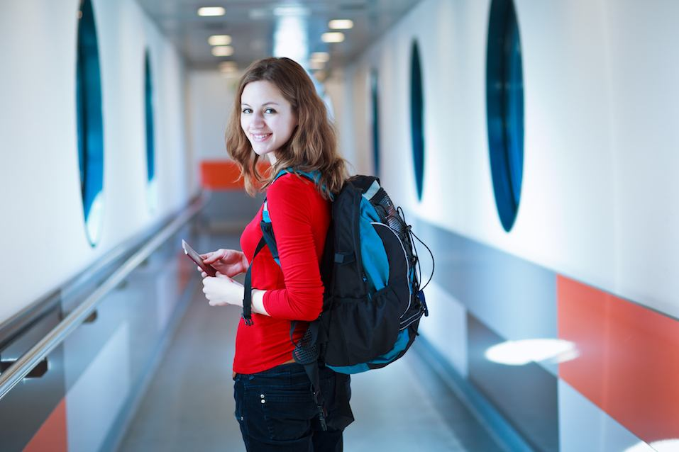 Woman in red shirt with book bag boarding a flight