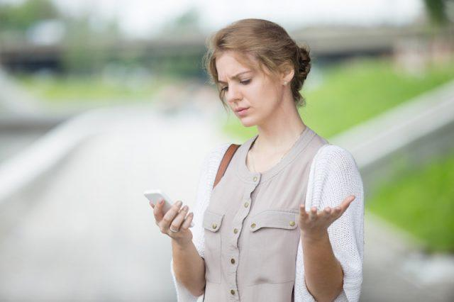 A woman looks at her phone stressfully.