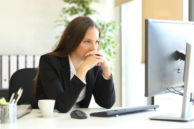 A woman glares at her computer.