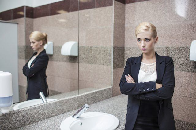 A woman cools off her temper in a bathroom.