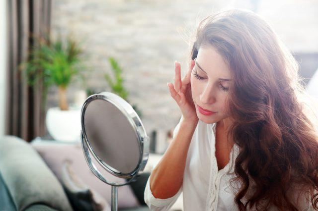 A woman inspects her face in a mirror.