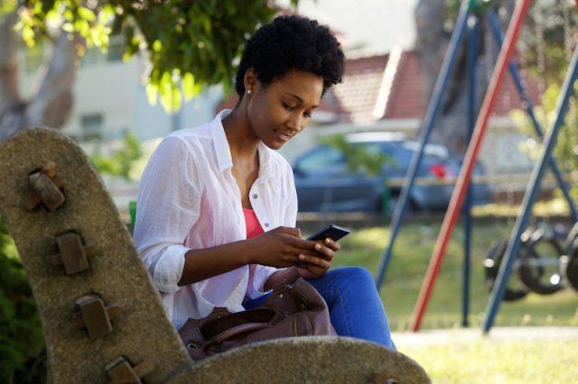 A woman sits at a park using her phone.