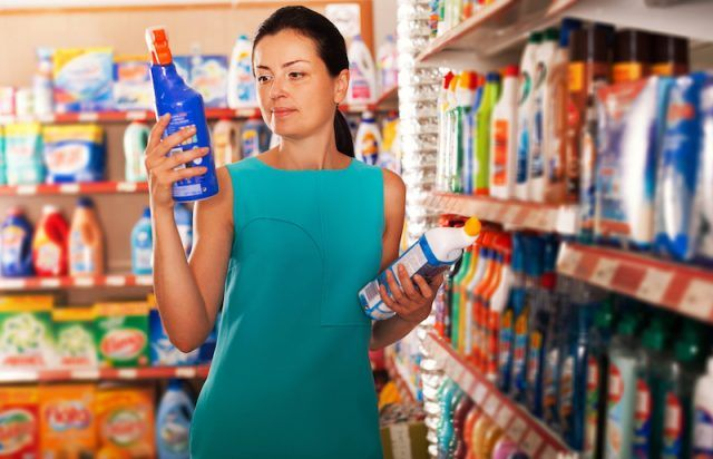 Woman reads the labels for chemical products.