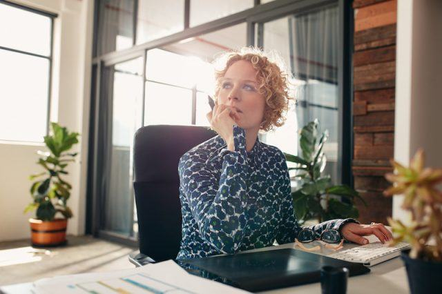 A woman sits in her office looking pensive.