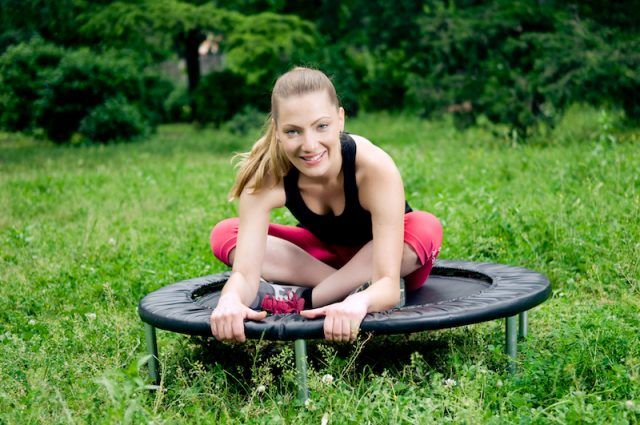 Woman sits happily on a trampoline.