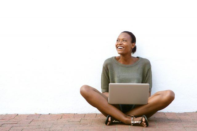 A woman sits happily with a computer on her lap.