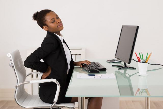 A woman sits with a backache at her computer.