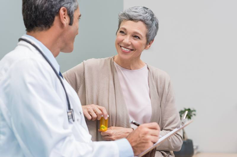 A doctor consults a senior female patient.