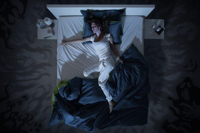 A woman tosses and turns in her bed.
