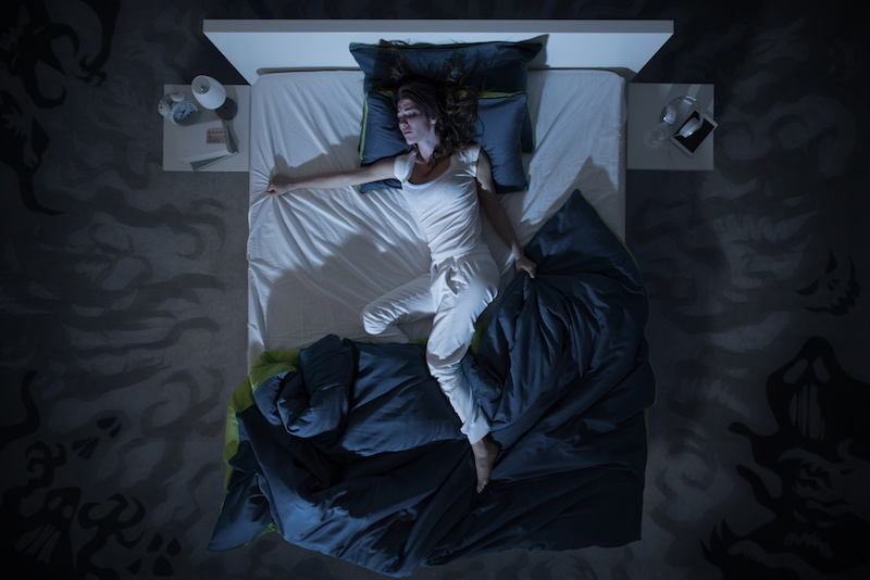 Woman tosses and turns in bed