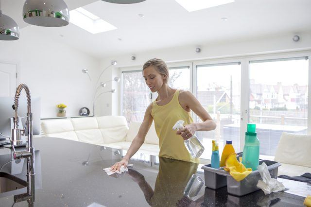 A woman uses wipes to clean her counter.