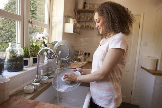 Woman washes her dishes in the morning.