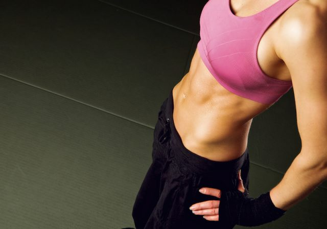 A woman with a pink sports bra and black pants stands with her hands on her hips.