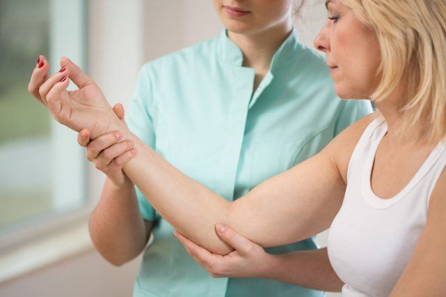 A woman works with her physical therapist.
