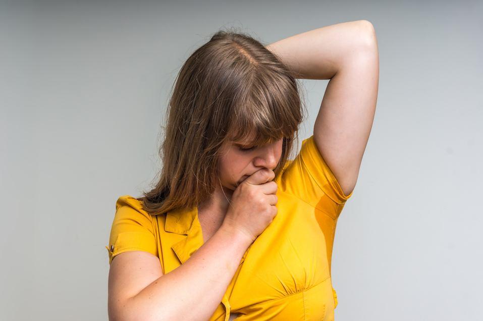 Woman with sweat stain under armpit in yellow dress