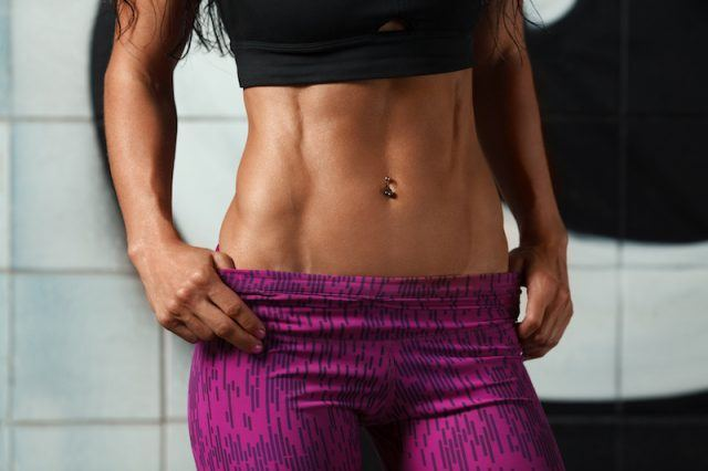 A woman with toned abs and purple pants stands in front of a wall.