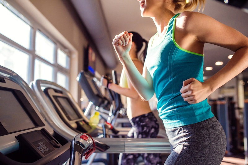 Two fit women running on treadmills in modern gym
