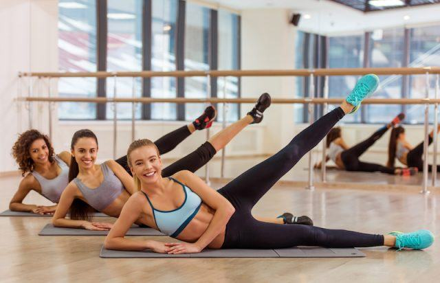 Three women stretch out their legs during a workout move